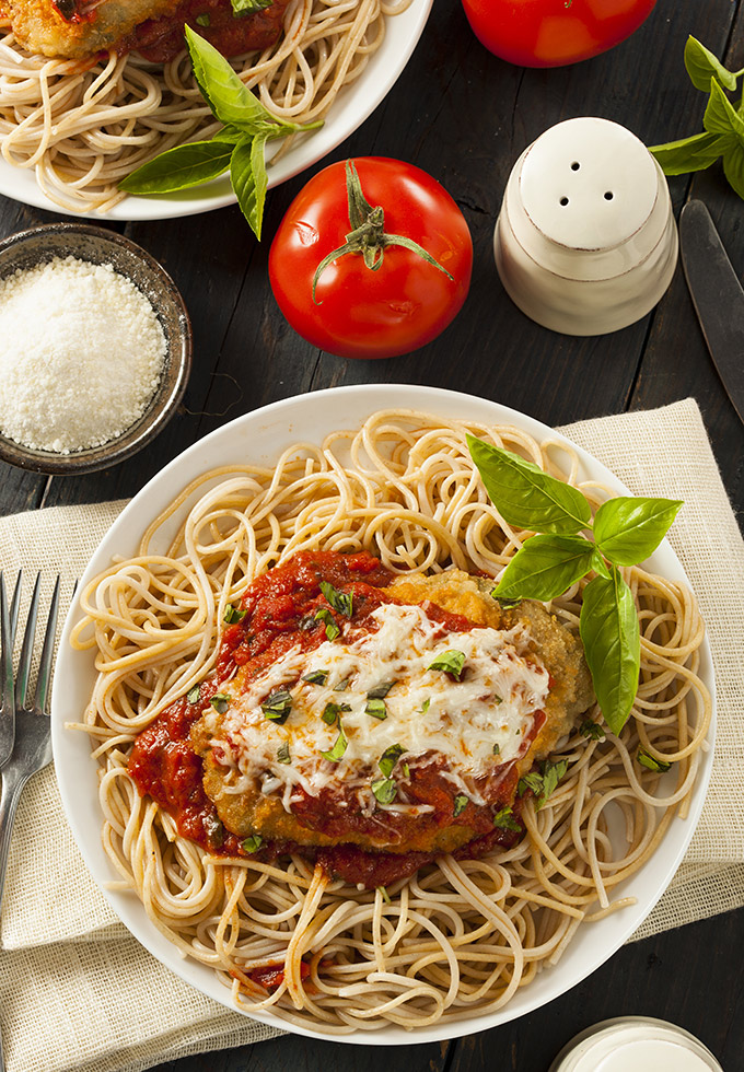 Chicken parmigiana over bed of spaghetti.