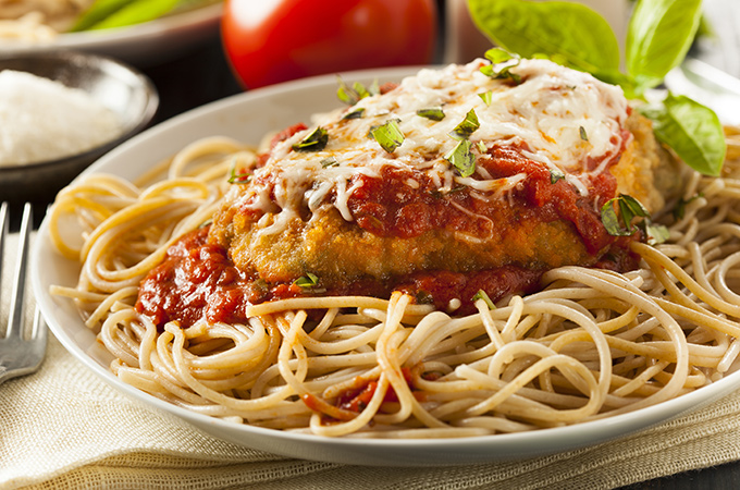 Chicken Parmigiana over a bed of spaghetti.